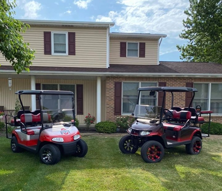 Two golf carts from Carts & Parts in Union City, IN facing each other in a home's front yard.