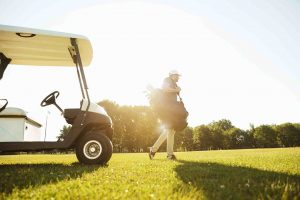 Male golfer walking with golf bag in front of golf cart.